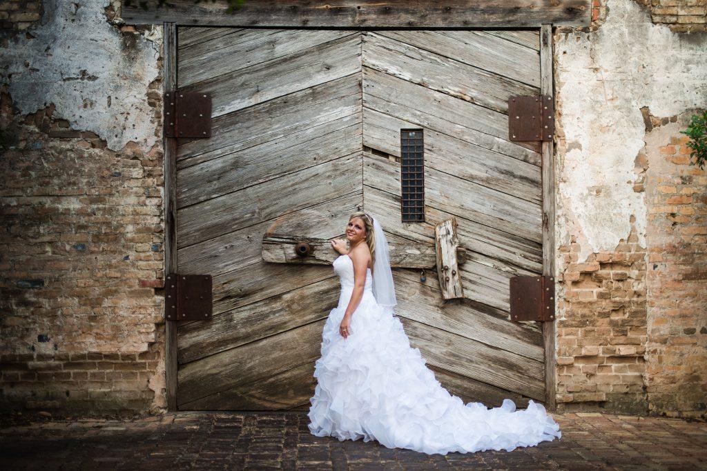 Wedding dress preservation bride in front of large barn door