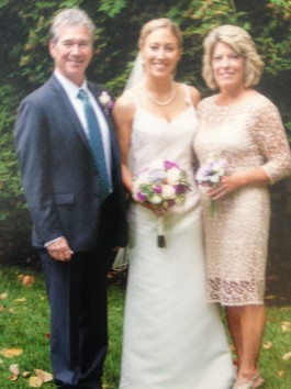 Catie with Mom and Dad at wedding. A second generation wears this wedding gown after expert transformation.